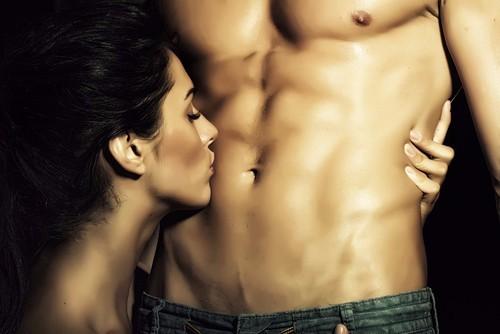 上半身裸の男性のお腹にキスをする女性